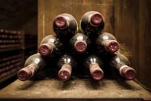 Lying Dusty Old Bottles Of Wine In The Italian Vineyard.