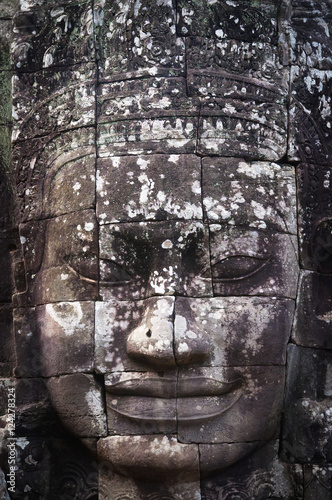 A face sculpture on a stone wall at angkor wat;Cambodia Poster