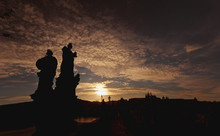Silhouette Of Two Statues And The Skyline In The Distance At Sunset;Prague, Czech Republic