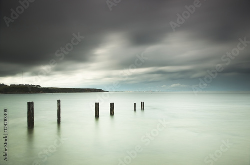 Wooden posts in a row in the shallow water along the coast under storm clouds;St. mary's bay northumberland england