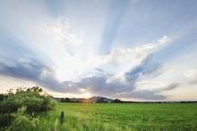 Sun Rays Through Clouds Over A Green Field;Thunder Bay Ontario Canada