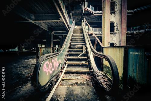 Fotografie, Obraz  Dramatic view of damaged escalators in abandoned building