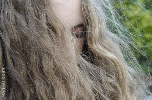 Portrait of a woman with eyes closed and long blond hair hanging over her face; Lake of the Woods, Ontario, Canada