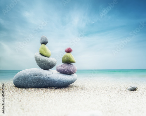 Cadres-photo bureau Zen pierres a sable Balancing colorful zen stones pyramid on sandy beach under blue sky. Beautiful nature and spiritual concept