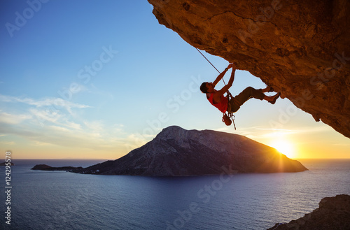 Cadres-photo bureau Marron Male climber on overhanging rock against beautiful view of coast below