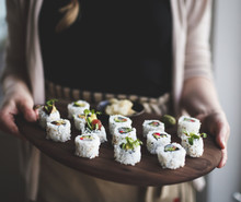 Woman Holding Wooden Tray With Sushi