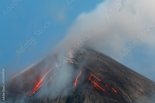 Staande foto Vulkaan Volcanic landscape of Kamchatka Peninsula: active Klyuchevskaya Sopka, view of top of a volcanic eruption - lava flows on slope of volcano; plume of gas, steam and ash from crater. Russian Far East.
