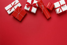 Christmas Gifts Presents On Red Background. Simple, Classic Red And White Wrapped Gift Boxes With Ribbon Bows Horizontal Top Border.