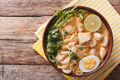 Fotografía  Malaysian laksa soup with chicken, egg, noodles and herbs close up in a bowl