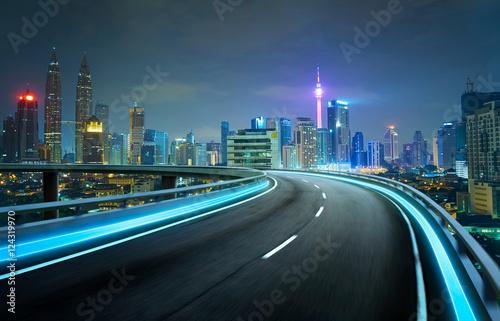 Keuken foto achterwand Nacht snelweg Blue neon light highway overpass motion blur with city skyline background , night scene .