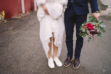 Bride In White Sport Shoes And Groom In Vinous Shoes Stand Side By Side, Groom Holds A Wedding Bouquet