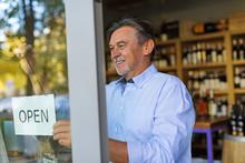 Wine Shop Owner Holding Open Sign