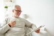 senior man in glasses reading newspaper at home