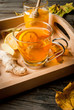 Warming ginger and lemon flavored hot drink or tea in a transparent cup in tray on a rustic wooden table, surrounded by leaves and a selection of ingredients - lemon, honey, ginger root. Copy space