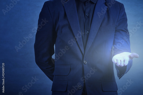 Fototapety, obrazy: man in formal wear touching empty virtual glass upturned palms  over dark blue background,business concept