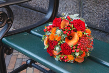 Red And Orange Bouquet Laying On A Bench