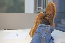 Man Relaxing At The Office With His Feet On The Table.