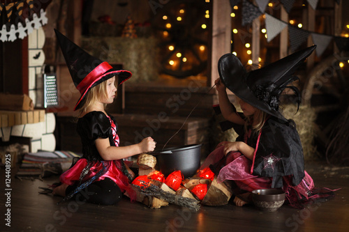 Fotografiet Two little Halloween  witches reading conjure above pot   childh