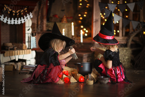 Fotografia, Obraz Two little Halloween  witches reading conjure above pot   childh