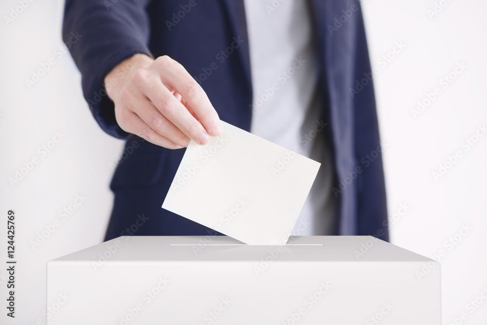 Fototapety, obrazy: Voting. Man putting a ballot into a voting box.