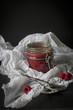 Jar of raw raspberry & chia jam in white paper before dark backg