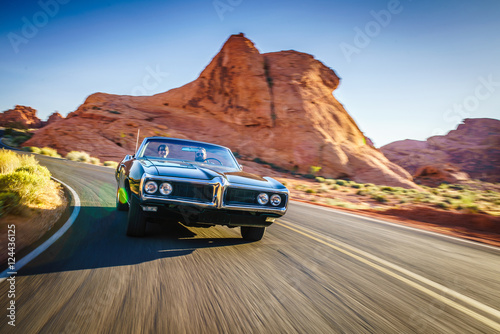 Obraz na plátne  couple driving together in cool vintage car through desert