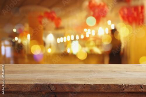 Fototapeta wooden table in front of blurred restaurant lights obraz na płótnie