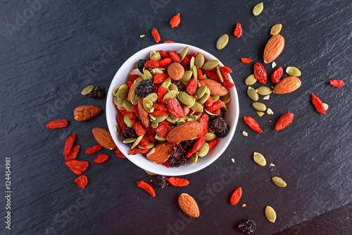 Valokuva  Nut mix snack with raisins, pumpkin seeds, almonds and goji berries on stone boa
