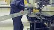 Metal bending machine. Worker operates bend sheet metal equipment at a metalworking factory. HD.