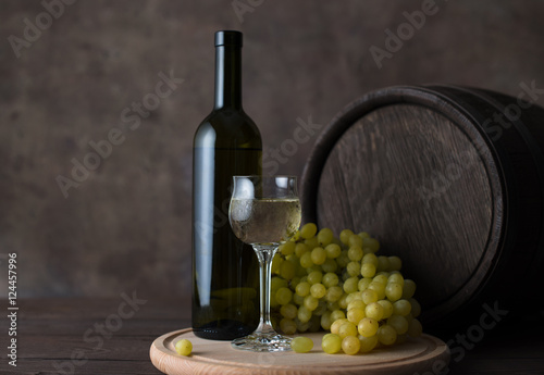 Foto op Canvas Chocoladebruin A bottle of white wine, a glass of white wine on a background of grapes and barrel on wooden table
