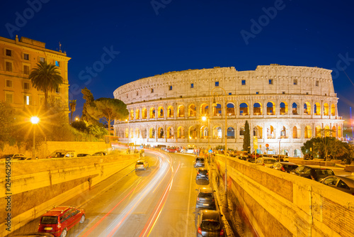 view of Colosseum illuminated at nighwith traffic lightst in Rome, Italy Wallpaper Mural