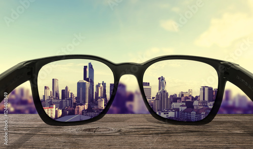 Wall Murals Asian Famous Place Sunglasses on wooden desk, focused on lens city view