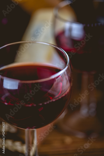 Glass of wine on wooden table, atmospheric composition
