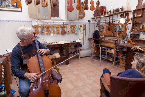 Keuken foto achterwand Muziekwinkel portrait of mature violin maker while testing the violins in his