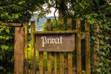 Vintage Private Sign In German Language On An Old Wooden Gate Grown With Moss And Ivy And Surrounded By Trees.
