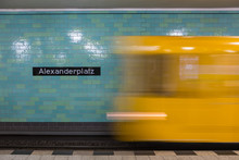 Yellow Subway Train In Motion. Berlin Alexanderplatz Sign Visible On The Wall Of Underground Station.