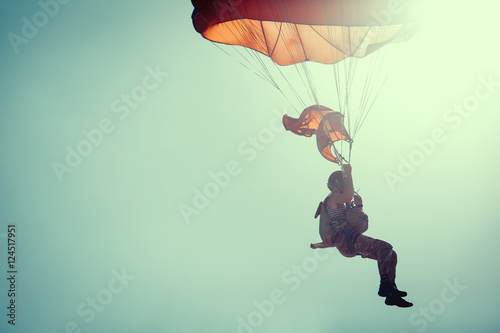 Deurstickers Luchtsport Skydiver On Colorful Parachute In Sunny Clear Sky.