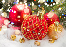 Red And Gold Christmas Ball In Snow Under Fir Tree With Lights Bokeh