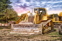 Large Bulldozer At Construction Site, Sunset In Background.