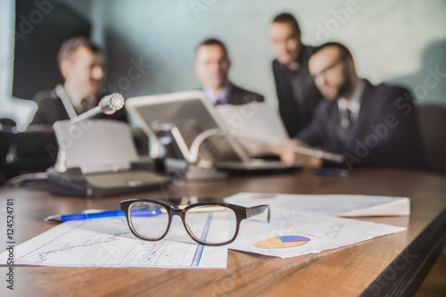 financial chart near dollars seen by unfocused glasses ( colleagues meeting to d Poster