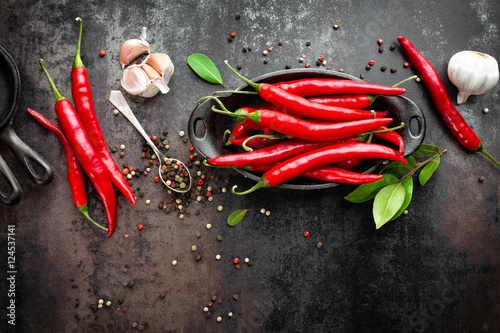 Photo Stands Hot chili peppers red hot chili pepper corns and pods on dark old metal culinary background