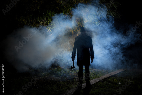 spooky man wih axe in the dark smoke filled forest Canvas Print