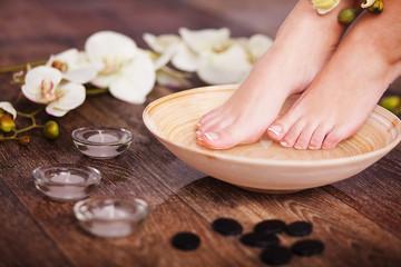 Obraz na płótnie Canvas Manicured female feet in spa pedicure procedure