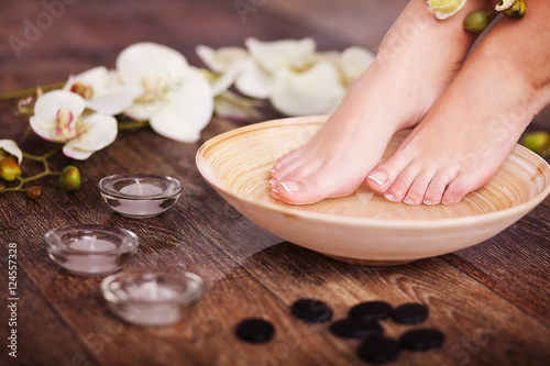 Manicured female feet in spa pedicure procedure