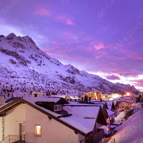Tuinposter Purper Sunset in alpine pass village.