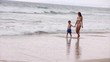 Young Mother and Her Son Walk Along the Coast