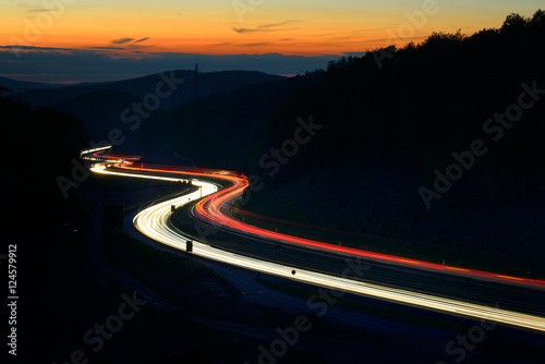 Winding Motorway through Hill Landscape at night, long exposure of headlights an Fototapete