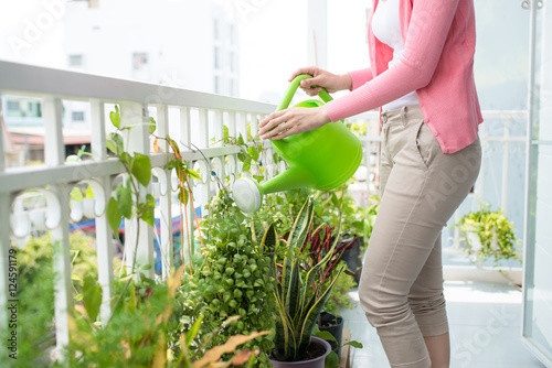 Fotografie, Obraz  Charming Young Asian Woman Watering Plant In Container On Balcon