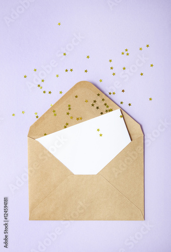 A brown envelope with party invitation letter and gold sequin stars a brown envelope with party invitation letter and gold sequin stars spilling out on to stopboris Images