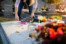 Woman Cleans A Grave.